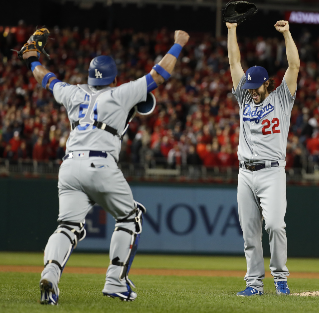 Los Angeles Dodgers pitcher Clayton Kershaw (22) and catcher Carlos Ruiz celebrate after Washington Nationals' Wilmer Difo struck out to end Game 5 of baseball's National League Division Series at Nationals Park early Friday, Oct. 14, 2016, in Washington. The Dodgers won 4-3. (AP Photo/Alex Brandon)
