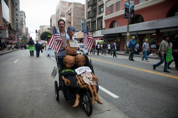 "A protester wheels ""aliens,"" including an E.T. doll, down the street in downtown Los Angeles, May 1, 2012"