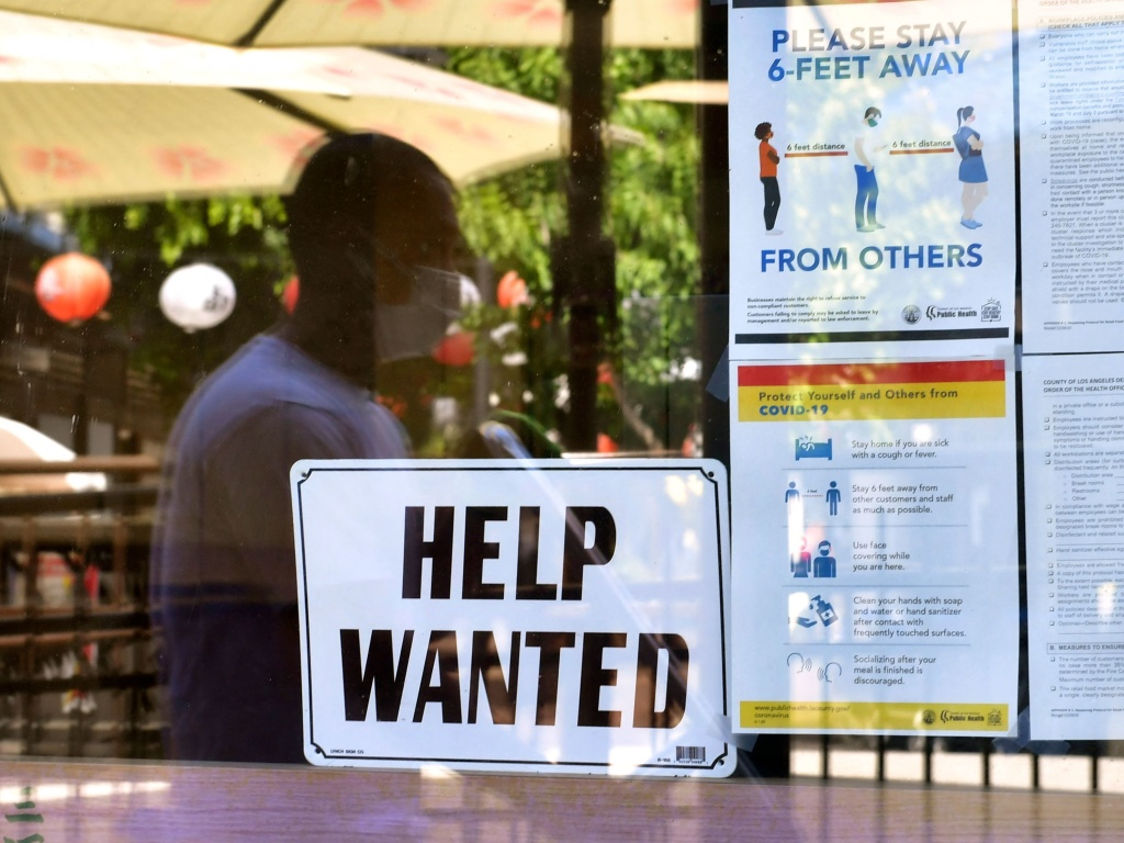 A 'Help Wanted' sign is posted beside Coronavirus health safety guidelines at a restaurant in Los Angeles on May 28. Businesses are desperate for workers even as millions remain unemployed. Republican governors blame a major unemployment benefit passed during the pandemic, saying it's dissuading people from rejoining the workforce.