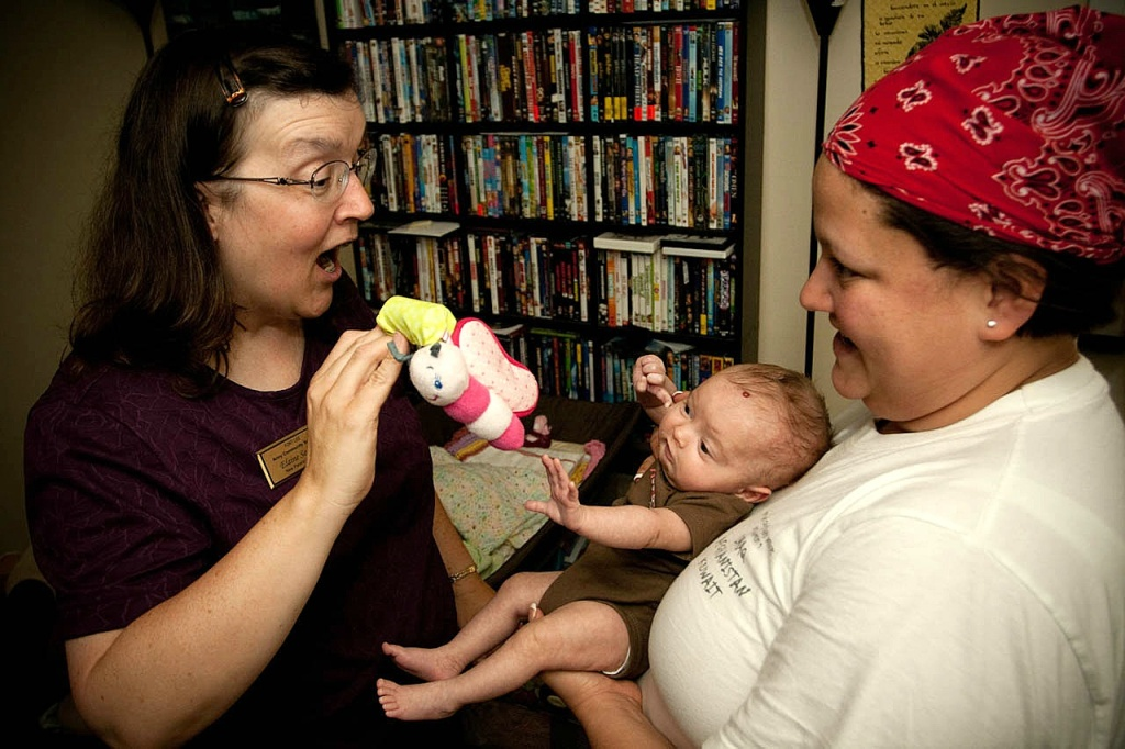Family members play with their baby.