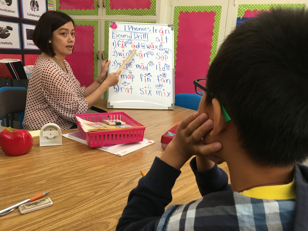 San Gabriel teacher Jenny Tan helps a student who's been in the U.S. less than a year learn the basics of English.