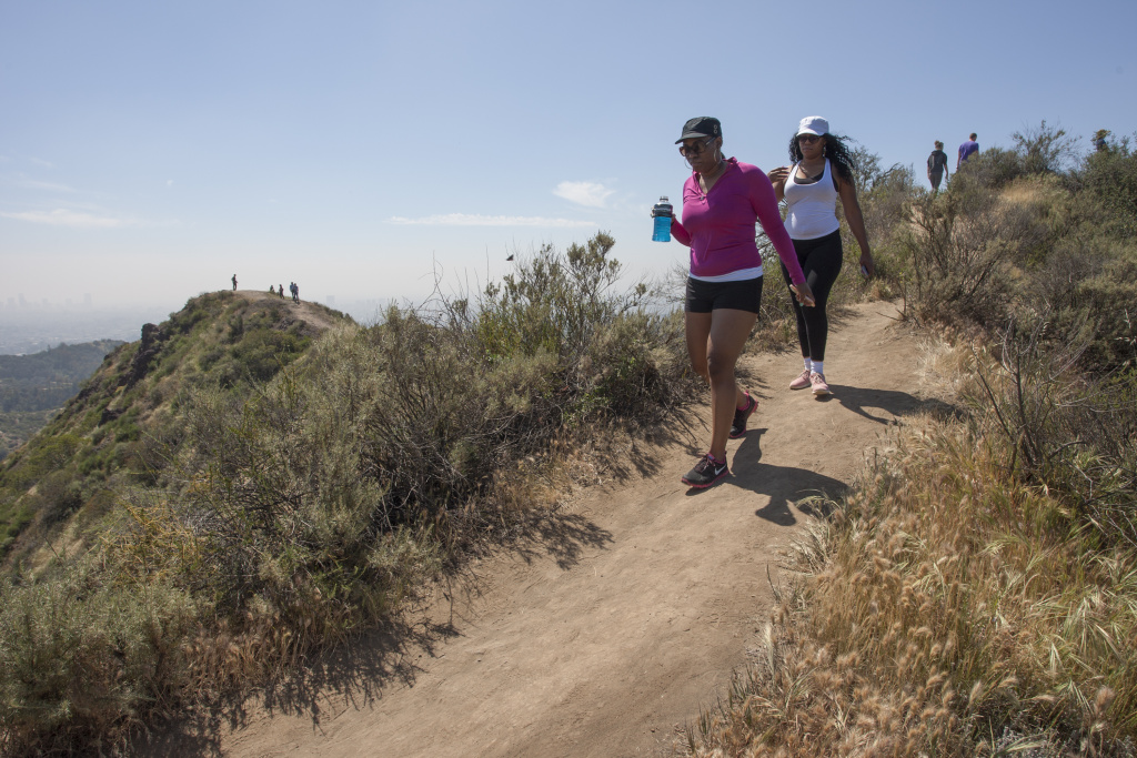 People hike along a ridge where vegetation quickly dried out in Griffith Park on March 29, 2015 in Los Angeles, California during a record-breaking heat wave.