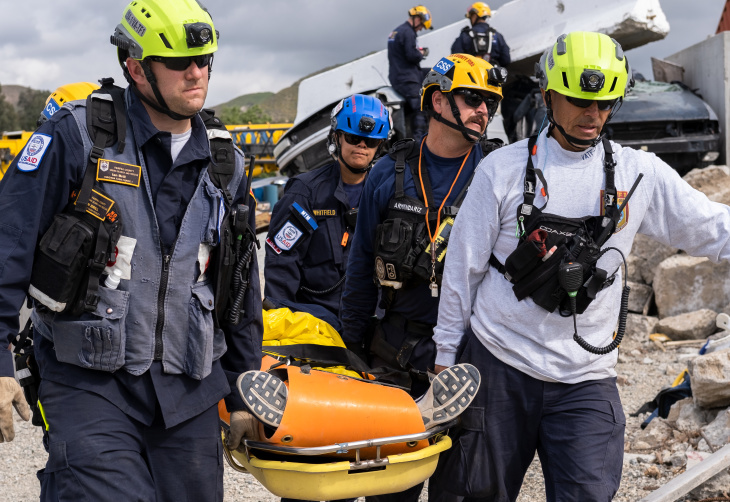 Urban Search and Rescue workers carry a victim away from a simulated earthquake near Castaic, California, in an April 3, 2019 training exercise.