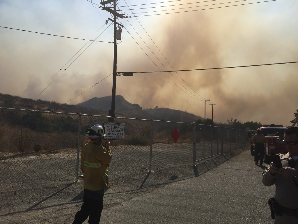 Firefighters respond to a wind-driven brush fire near the 91 Freeway and 241 toll road on Monday, Oct. 9, 2017.