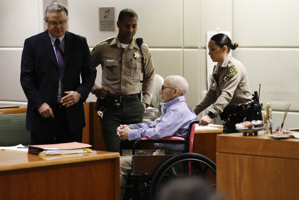 Real estate heir Robert Durst, center, is brought into a courtroom in the wheelchair for a hearing Wednesday, Dec. 21, 2016, in Los Angeles. At left is his attorney David Chesnoff.