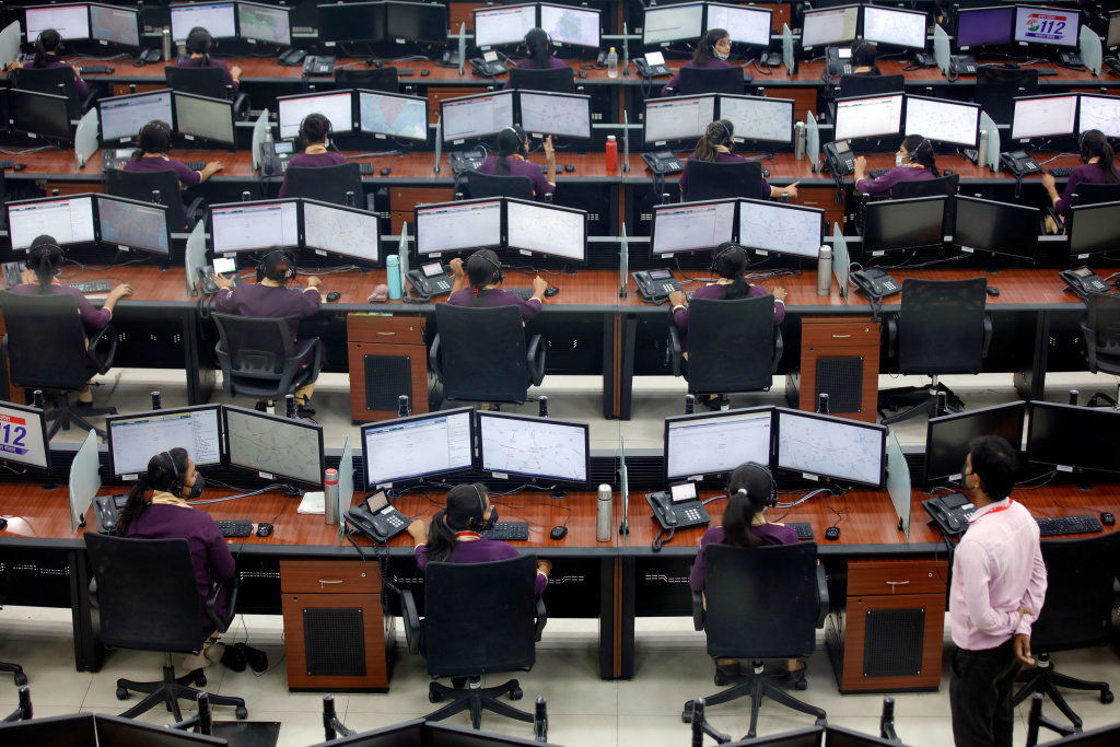 Employees work in a call center run by Uttar Pradesh state police in Lucknow, India, in April.