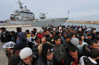 Tunisian would-be immigrants wait for their belongings after disembarking from the
