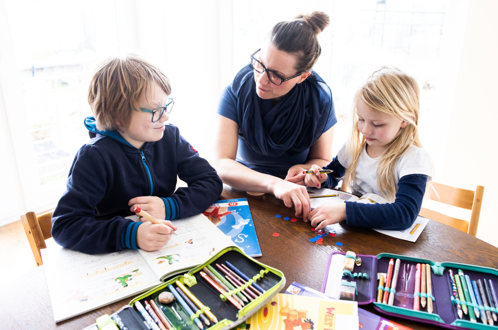 A mother helps her nine-year-old son and six-year-old daughter to do school homework.