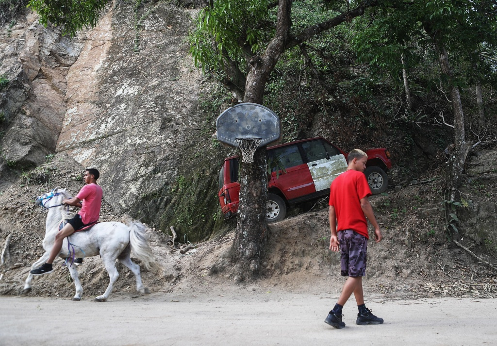 A resident rides a horse along a road that was hit by a mudslide during Hurricane Maria on October 21, 2017 in Utuado, Puerto Rico.
