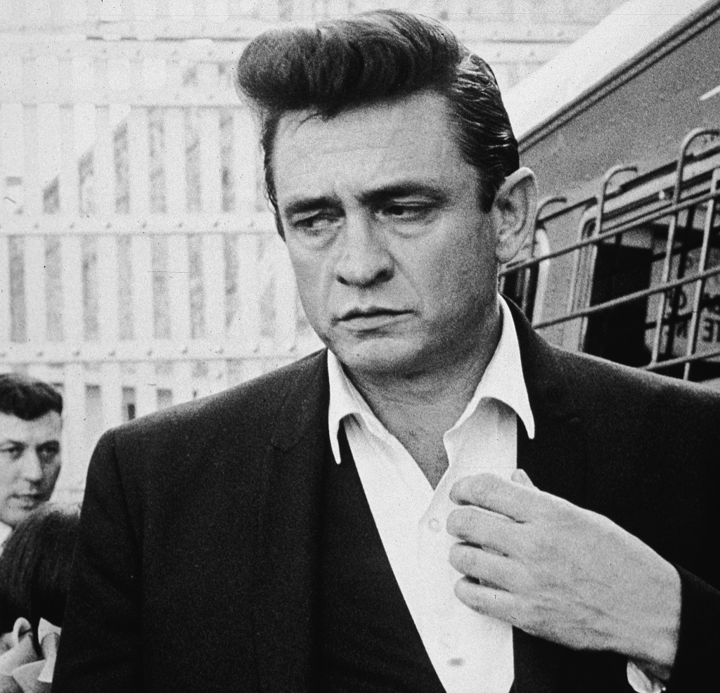 American country singer and songwriter Johnny Cash (1932 - 2003) walks inside the gates of Folsom Prison, preparing to perform his fourth concert for inmates there, California, 1964.