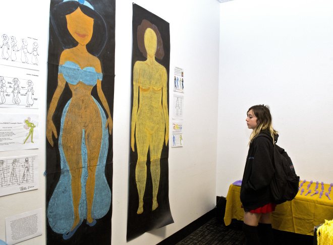 In this Friday, Dec. 9, 2016, photo, Ajani Russell poses with her artwork