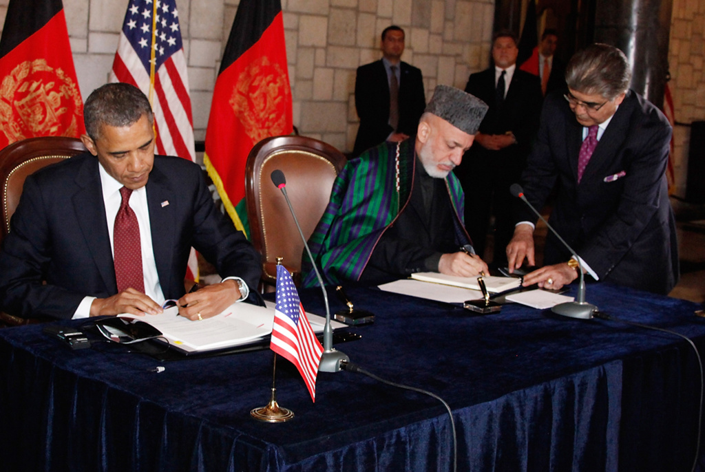In a handout image released by the Afghan Presidents Office, US President Barack Obama (L) signs documents with Afghanistan President Hamid Karzai (R), during their meeting on May 2, 2012 in Kabul, Afghanistan.
