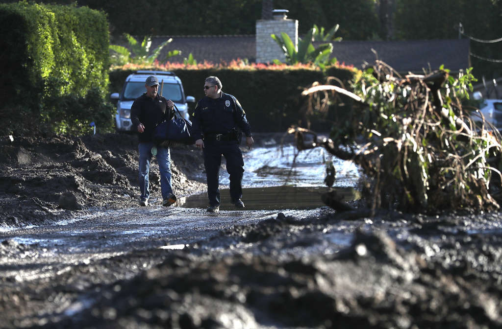 A police officer escorts a resident through a neighborhood that was destroyed by a mudslide on January 12, 2018 in Montecito, California.