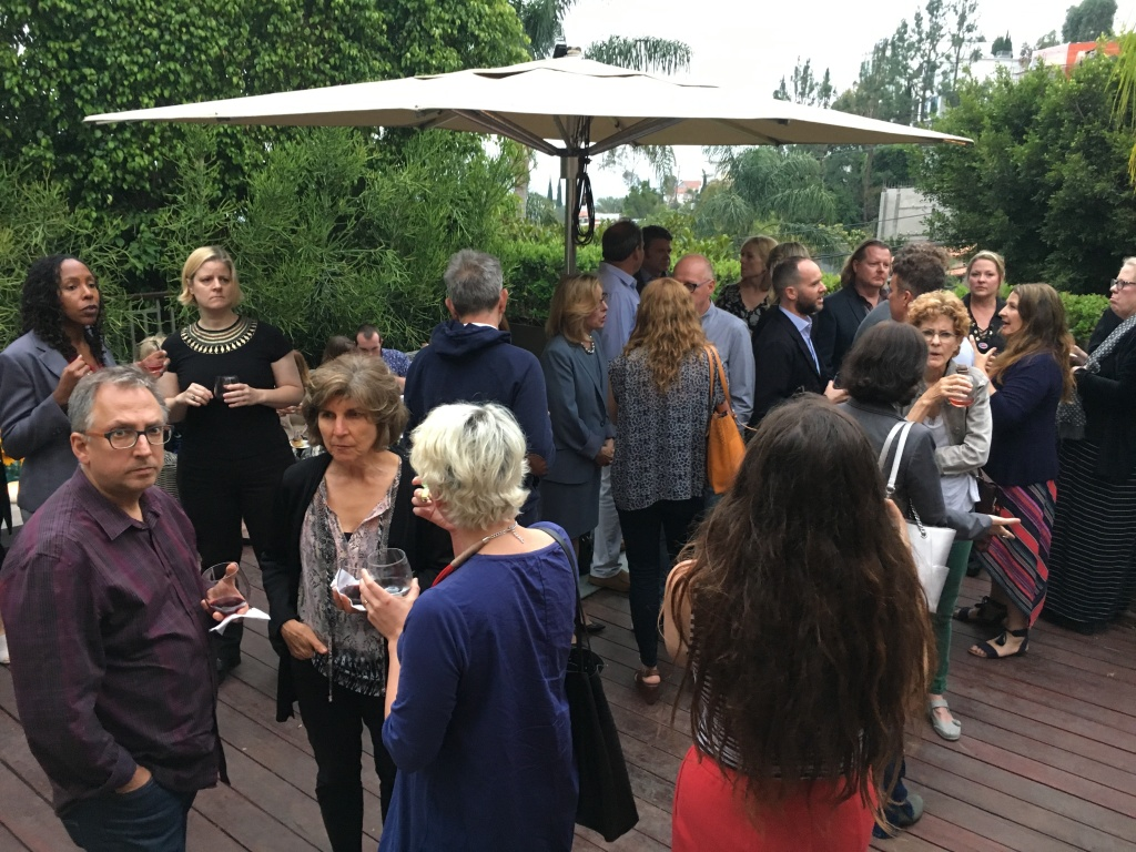 Members of Indivisible 2.9 mingle with celebrities on the deck of a home in the Hollywood Hills.