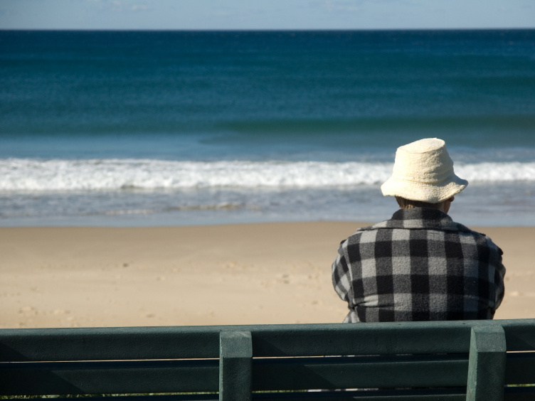 A man in his seventies sits on a bench overlooking the ocean.