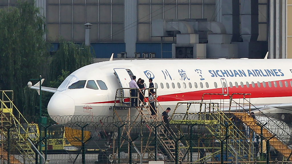 Employees checking a Sichuan Airlines Airbus A319 on Monday, after an emergency landing in Chengdu in China's northwestern Sichuan province. A cockpit window that broke mid-flight has been covered up; the flight's co-pilot was partially sucked out of the window in the accident.