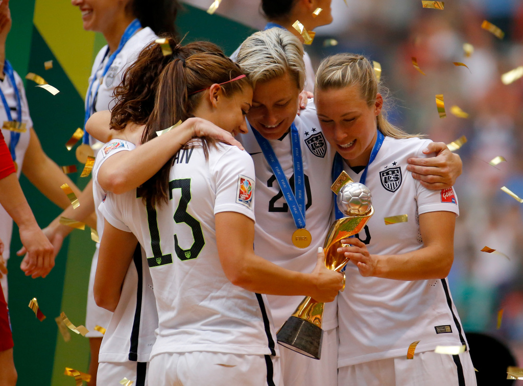 Alex Morgan #13, Lauren Holiday #12, Abby Wambach #20 and Whitney Engen #6 of the United States of America hold the World Cup Trophy after their 5-2 win over Japan in the FIFA Women's World Cup Canada 2015 Final at BC Place Stadium on July 5, 2015 in Vancouver, Canada. Morgan and four other top female players have accused U.S. Soccer of wage discrimination.