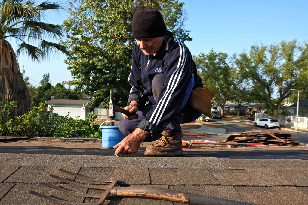 In this file photo, roofer Michal Swiderski works on putting a new roof on his home in the Panorama City section of Los Angeles on Saturday, Oct. 17, 2015. For homeowners who rely on professionals to do the work, the L.A. City Attorney's office issued a warning to guard against unlicensed contractors, who will often approach homeowners after a storm.