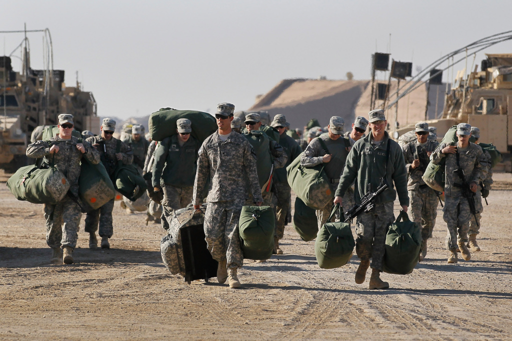 U.S. Army soldiers from the 2-82 Field Artillery, 3rd Brigade, 1st Cavalry Division, carry their bags to shipping containers as they prepare to leave Camp Adder as the base is readied to be handed back to the Iraqi government on December 6, 2011 at Camp Adder, near Nasiriyah, Iraq.