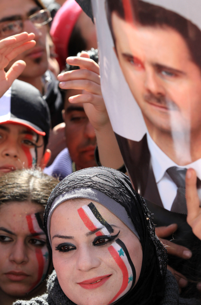 Supporters of Syria's President Bashar Assad (portrait) attend a pro-regime rally in central Damascus on Feb. 5, 2012.