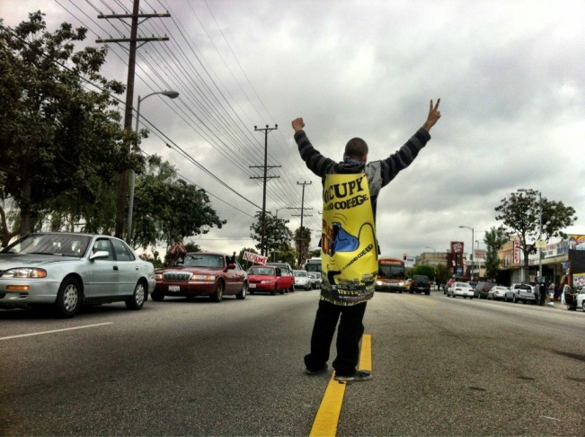 An occupy protestor moves past police on Hill St in Downtown Los Angeles on May 1st, 2012.