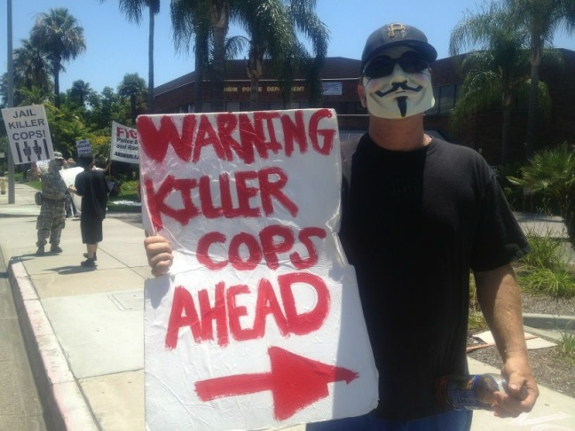 A protester holds a sign pointing toward the Anaheim Police Department on Sunday afternoon.